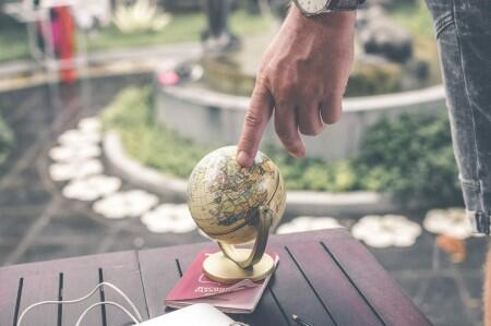 finger pointing to small globe
